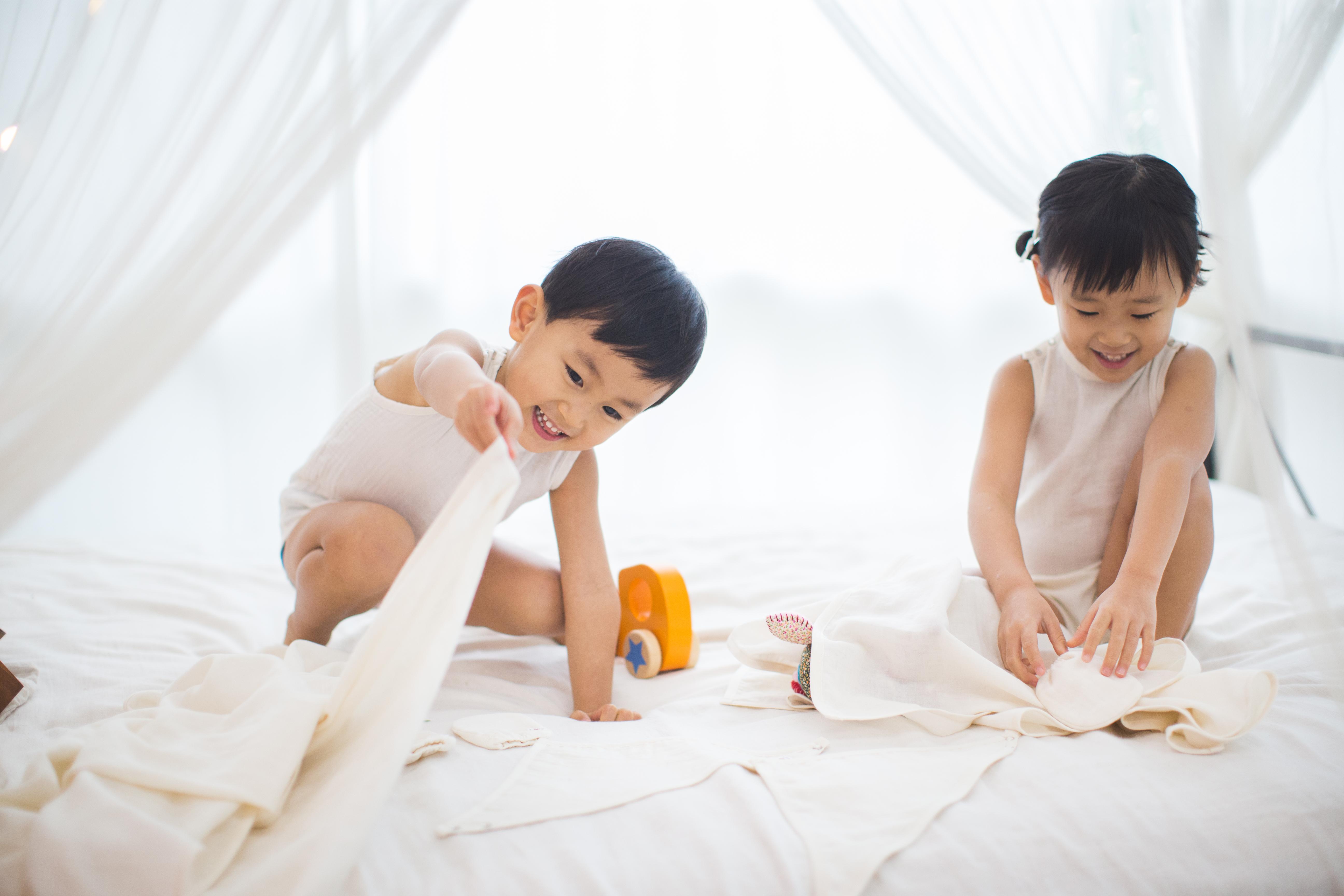 Toddler boy is lifting Pokka Kids dye free GOTS certified organic cotton blanket while wearing sleeveless baby bodysuit